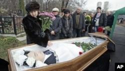 Mẹ của luật sư Sergei Magnitsky đứng cạnh linh cữu của ông trong tang lễ tại một nghĩa trang ở Moscow, 20/11/2009