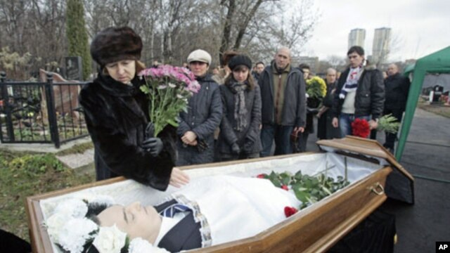 Nataliya Magnitskaya (L), mother of Sergei Magnitsky, grieves over her son's body during his funeral at a cemetery in Moscow November 20, 2009.