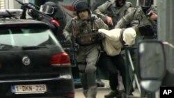 Polisi Belgia saat melakukan penggerebekan di Molenbeek, pinggiran Brussels, yang berhasil menangkap terduga teroris paling dicari di Eropa, Salah Abdeslam, Jumat (18/3).