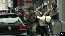 Salah Abdeslam emmené par des policiers lors d'un raid dans le quartier Molenbeek à Bruxelles, en Belgique, 18 Mars 2016.