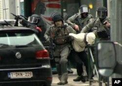 Cảnh sát áp giải Salah Abdeslam ra xe cảnh sát trong một cuộc đột kích ở khu Molenbeek của thủ đô Brussels, Bỉ, ngày 18 tháng 3, 2016.