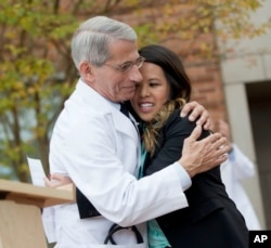 FILE - Dr. Anthony Fauci, head of NIH's National Institute of Allergy and Infectious Diseases, hugs Nina Pham as she's discharged from treatment in Bethesda, Maryland, Oct. 24, 2014.