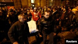 Demonstran anti-pemerintah mengangkat mayat yang ditutupi kain dalam proses pemindahan belasan mayat dari lobby hotel ke rumah sakit.