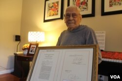 World War II veteran Celestino Almeda, 100, displays the documentation of his Congressional Gold Medal. He became a U.S. citizen in 1996. (I. Basco/VOA)