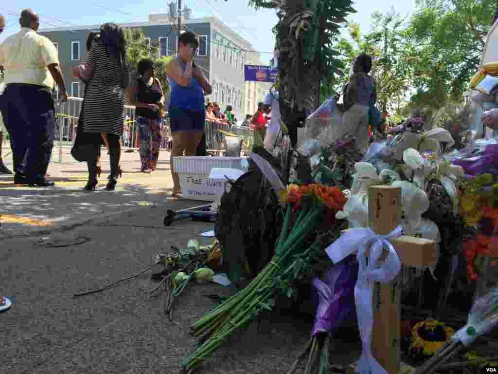 Warga yang berkabung meletakkan karangan bunga di luar Gereja AME Emanuel di Charleston, South Carolina (21/7). (VOA/Amanda Scott)