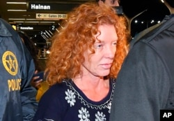 Tonya Couch is taken by authorities to a waiting car after arriving at Los Angeles International Airport, Dec. 31, 2015.
