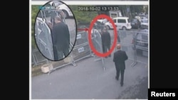 A still image taken from CCTV video and obtained by TRT World claims to show Saudi journalist Jamal Khashoggi, highlighted in a red circle by the source, as he stands with his fiancee Hatice Cengiz outside the Saudi Arabia's Consulate in Istanbul, Turkey