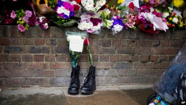 FILE - Military boots are displayed outside London's Woolwich Barracks in tribute to British soldier Lee Rigby killed nearby in May.