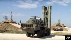 FILE - A photo made from the footage taken from the Russian Defense Ministry official website on Nov. 27, 2015, shows Russian S-400 air defense missiles being deployed at the Hemeimeem air base in Syria.