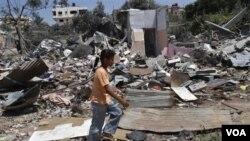 Seorang anak perempuan Palestina berjalan di antara reruntuhan bangunan yang hancur akibat serangan pesawat Israel (19/8).
