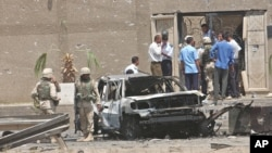 FILE - U.S. troops inspect a destroyed vehicle at the main gate of the Jordanian Embassy after a bomb attack, Aug. 7, 2003, in Baghdad, Iraq, one of the crimes for which 10 men were executed Saturday.