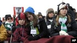 一批群众2012年1月26日在华盛顿纪念碑附近举行的一个反对枪支暴力的集会上听取一个演讲者演讲