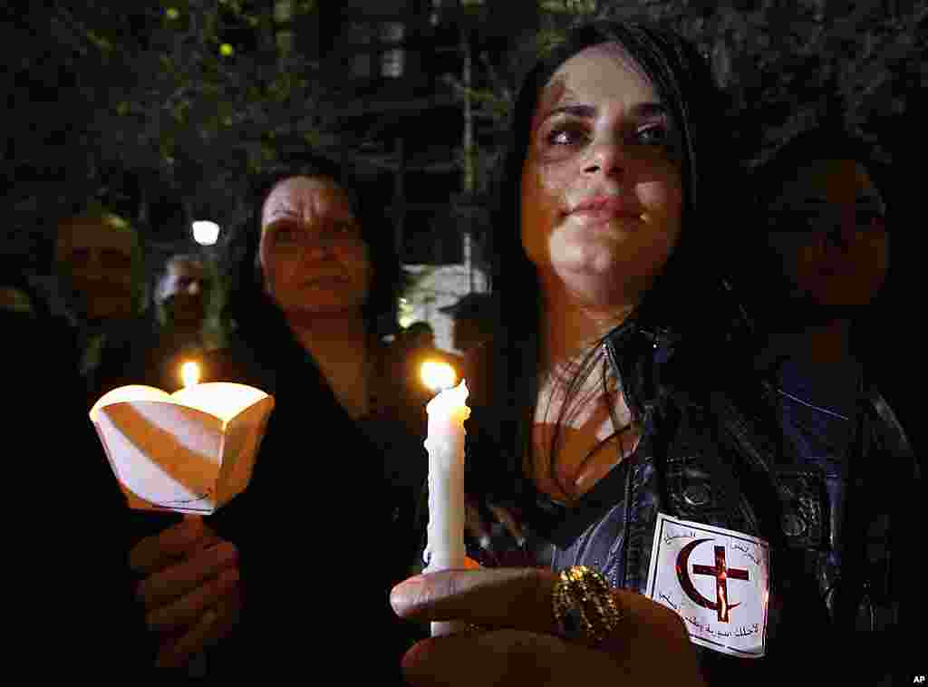Syrian women hold candles during a vigil after a mass prayer for civilians and security officers killed in Damascus Saturday by explosions, Damascus, Syria, March 21, 2012. (AP)