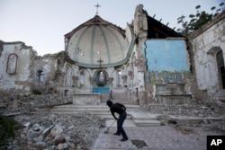 FILE - A man sweeps an exposed tiled area of the earthquake-damaged Santa Ana Catholic church, where he now lives, in Port-au-Prince, Haiti, Jan. 12, 2013.