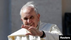 FILE - Pope Francis waves as he arrives to lead his Wednesday general audience in Saint Peter's Square at the Vatican.