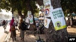 Des écolières défilent devant les affiches de la campagne présidentielle, à Ouagadougou le 6 novembre 2020, lors de la campagne présidentielle avant les élections présidentielles du 22 novembre 2020.