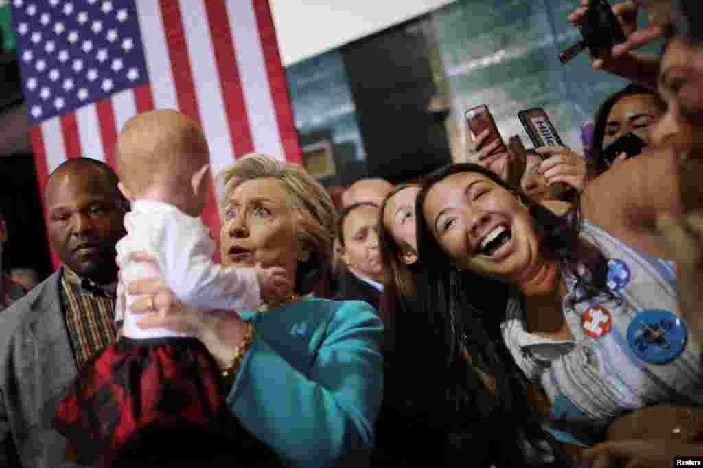 បេក្ខជនប្រធានាធិបតីគណបក្សប្រជាធិបតេយ្យលោកស្រី Hillary Clinton លើកទារកមួយអំឡុងពេលយុទ្ធនាការឃោសនានៅក្រុង Lake Worth រដ្ឋ Florida។