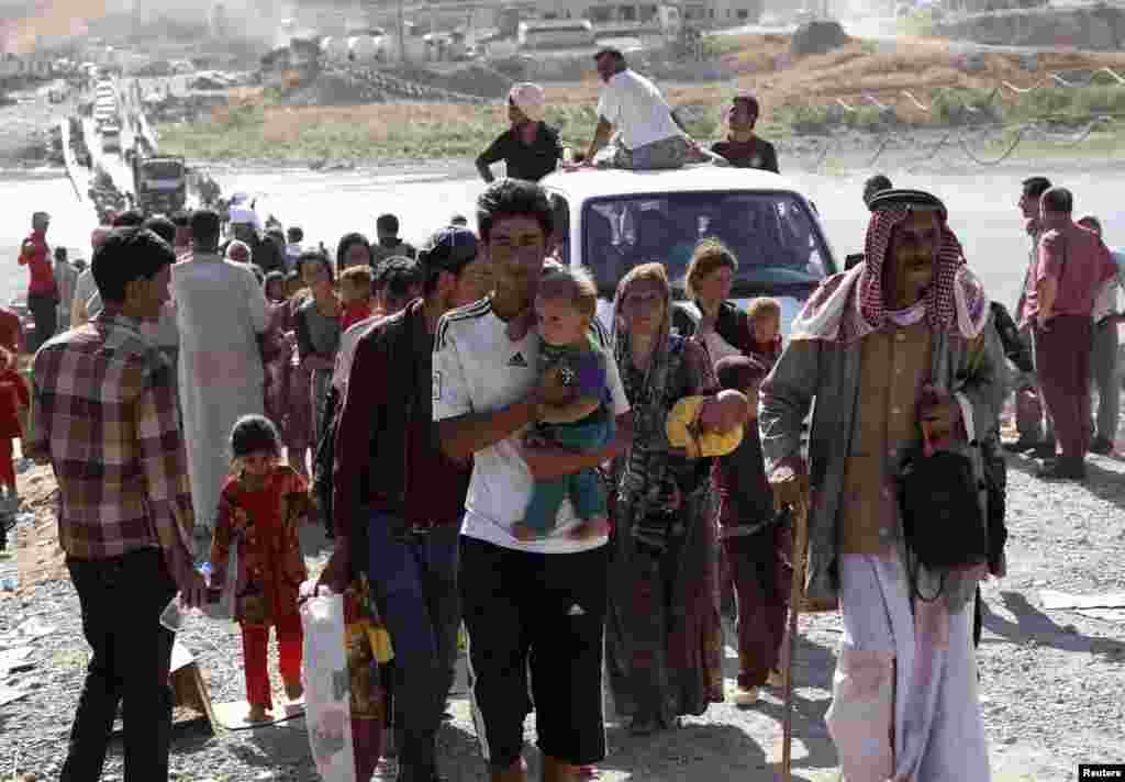 Displaced people from the minority Yazidi sect, fleeing violence in the Iraqi town of Sinjar, re-enter Iraq from Syria at the Iraqi-Syrian border crossing in Fishkhabour, Dohuk province, Aug. 10, 2014.