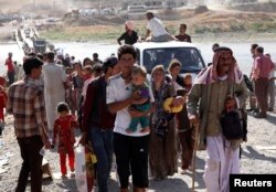 FILE - Displaced people from the minority Yazidi sect, fleeing violence in the Iraqi town of Sinjar, re-enter Iraq from Syria at the Iraqi-Syrian border crossing in Fishkhabour, Dohuk province, Aug. 10, 2014.