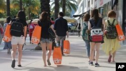 FILE - Tourists carry shopping bags as they walk along Lincoln Road Mall, a pedestrian area featuring retail shops and restaurants in the South Beach section of Miami Beach, Florida, Feb. 3, 2016.