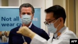 Governor Gavin Newsom watches as the Pfizer-BioNTech COVID-19 vaccine is prepared by Director of Inpatient Pharmacy David Cheng at Kaiser Permanente Los Angeles Medical Center in Los Angeles, California on December 14, 2020.