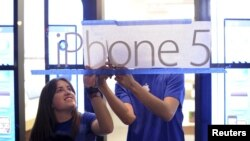 Apple employees hang an iPhone 5 sign at one of the company's retail locations shortly before sales began in San Francisco, California, September 21, 2012. Apple fans queued around city blocks worldwide on Friday to get their hands on the new iPhone 5 - but grumbles about inaccurate maps tempered the excitement.