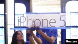 Empleados de Apple cuelgan un cartel promocional del iPhone 5 en uno de puntos de venta de la compañía, poco antes de que las ventas comenzaron en San Francisco, California.
