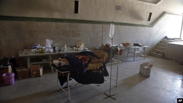 Mahmoud, 21, a Palestinian resident of Syria, rests in a field hospital after he was found Monday, August 6, 2012, with three gunshot wounds on the outskirts of Aleppo, Syria.
