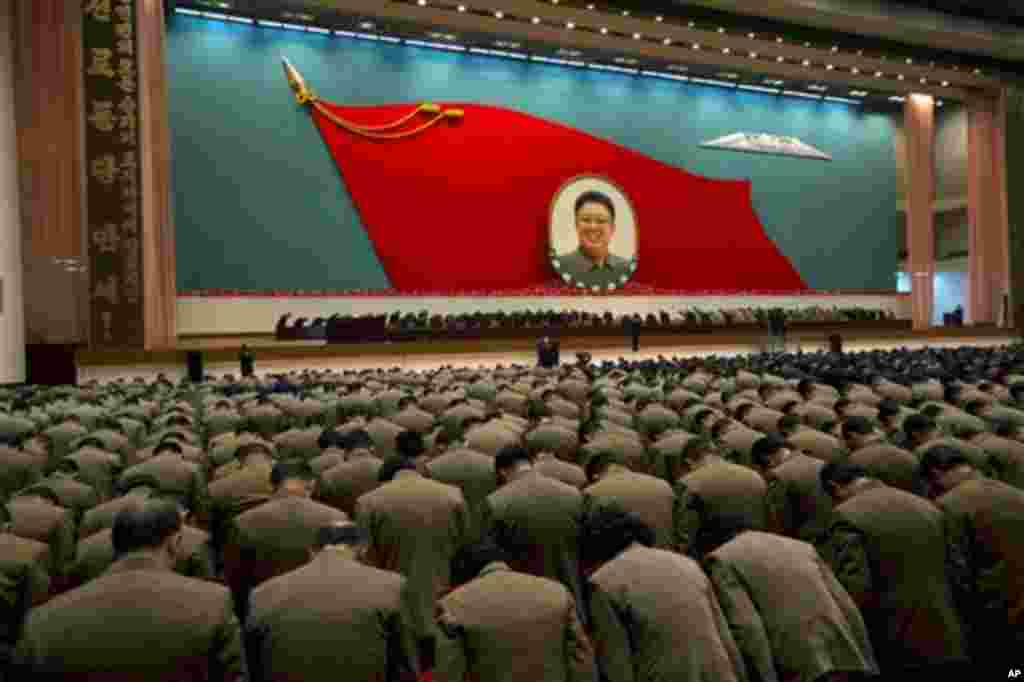 North Korean military officers bow at an image of late North Korean leader Kim Jong Il during a national meeting of top party and military officials on the eve of Kim's first death anniversary in Pyongyang, North Korea, Sunday, Dec. 16, 2012.