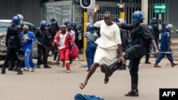 An anti-riot police man in Zimbabwe tackles a woman with his boot as they dispersed a crowd gathered to hear an address by leader of the MDC (Movement for Democratic Change) Alliance, Nelson Chamisa at Morgan Tsvangirai House, the party headquarters, in H