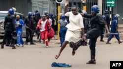 FILE: Ipholisa ligwenxa owesifazane phandle kwamawofisi ebandla leMDC elikhokhelwa nguMnu. Nelson Chamisa. (Photo by Jekesai NJIKIZANA / AFP)