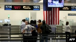 FILE - International travelers wait at a U.S. Customs and Border Protection checkpoint after arriving at Miami International Airport in Florida. Iran objects to a new U.S. law restricting visa-free travel rights for dual citizens and others.