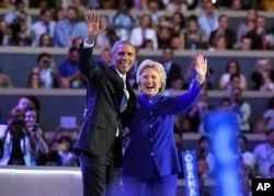 President Barack Obama and Democratic Presidential candidate Hillary Clinton wave together during the third day of the Democratic National Convention in Philadelphia , July 27, 2016.