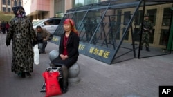 FILE - An Uighur woman rests near a cage protecting heavily armed Chinese paramilitary policemen on duty in Urumqi in China's northwestern region of Xinjiang, May 1, 2014. Uighur homeland has been blanketed with stifling surveillance, from armed checkpoin