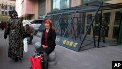 2014年5月1日,一名维吾尔族妇女在一个由中国武警重兵把守的大楼入口处休息。