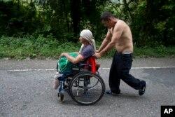 El migrante hondureño Omar Orella empuja a su compañera Nery Maldonado Tejeda en una silla de ruedas, mientras viajan con cientos de otros hondureños que se dirigen a EE.UU., cerca de Chiquimula, Guatemala, el martes 16 de octubre de 2018.