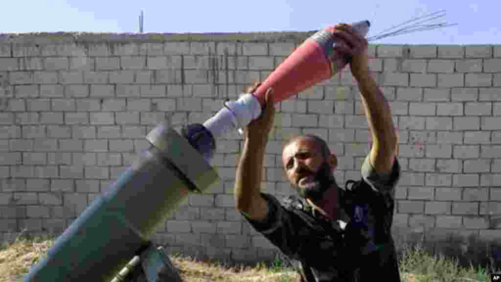 Free Syrian army fighter moments before firing a heavy mortar toward the airport in Aleppo, Syria, Sept. 2, 2013.
