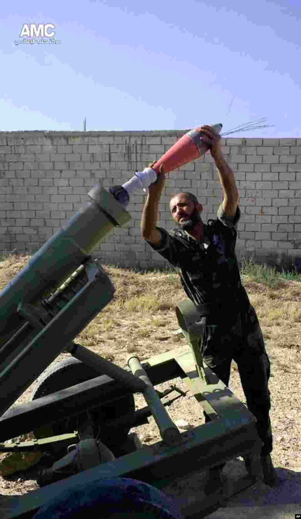 This citizen journalism image provided by Aleppo Media Center AMC shows a Free Syrian army fighter moments before firing a heavy mortar toward the airport in Aleppo, Syria, Sept. 2, 2013.