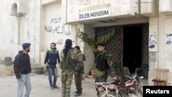 FILE - Rebel fighters stand outside Idlib museum in Idlib, Syria, after Islamist rebel fighters took control of the area, April 1, 2015.