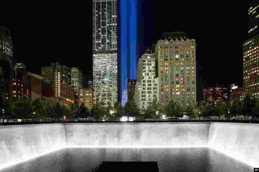 The Tribute in Light rises behind buildings adjacent to the 1 World Trade Center and a reflecting pool at the National September 11 Memorial in New York, Sept. 8, 2014.