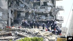 "Para petugas penyelamat masih terus melakukan pencarian korban di antara puing-puing gedung apartemen ""Champlain Towers South condominium"" di Miami, Florida yang roboh hari Kamis (24/6)."