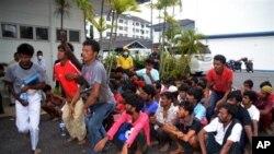 來自緬甸和孟加拉國的船民被送到馬來西亞的一個警察局。