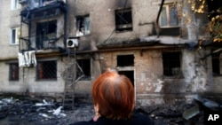 Seorang perempuan menangis di depan bangunan apartemennya yang hancur di kota Donetsk, Ukraina Timur (17/9).