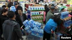People line up to buy cartons of bottled water at a supermarket after reports on heavy levels of benzene in local tap water, in Lanzhou, Gansu province, April 11, 2014.