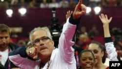 资料照片:在伦敦奥运会上,时为美国奥运女子体操队主教练的戈德尔特和队员们庆祝夺取金牌。(2012年7月31日)