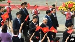 中国国家主席习近平和越南共产党总书记阮富仲前往参加会谈,向欢迎群众招手(2017年11月12日)