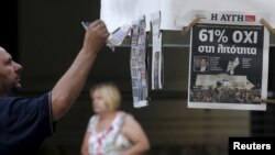 A man looks at newspapers showing the results of yesterday's referendum in central Athens, Greece, July 6, 2015. Greeks overwhelmingly rejected conditions of a rescue package from creditors on Sunday, throwing the future of the country's euro zone members. (REUTERS/Christian Hartmann)