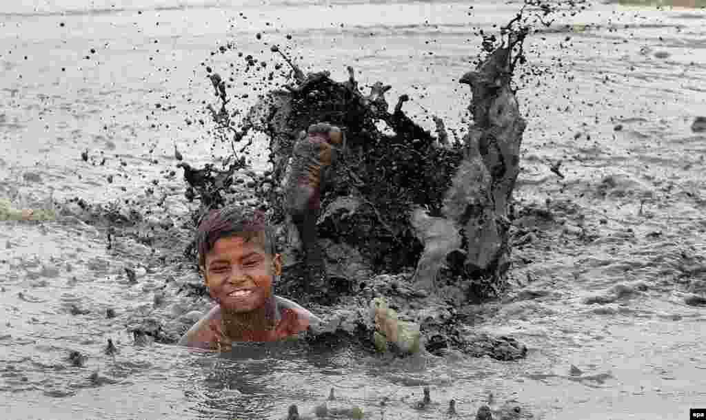 A boy swims in a dirty pond on a hot summer day in New Delhi, India.