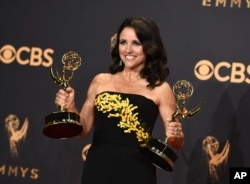 "FILE - Julia Louis-Dreyfus poses in the press room with her awards for outstanding lead actress in a comedy series and outstanding comedy series for ""Veep"" at the 69th Primetime Emmy Awards at the Microsoft Theater in Los Angeles, Sept. 17, 2017."