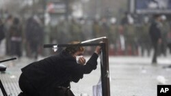 A woman takes cover during clashes after the start of a national strike in Santiago, Chile, August 24, 2011